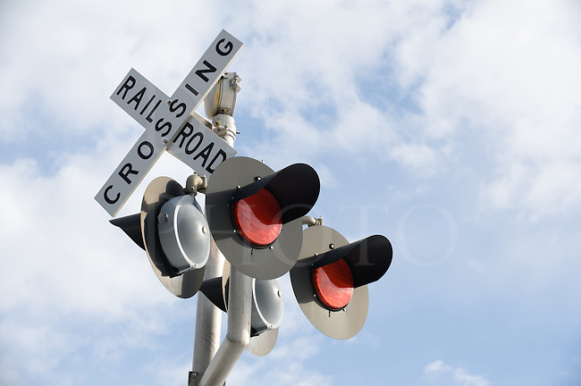 Railroad crossing sign, modern and new electronic version equipment, shot low angle with sky as background.
