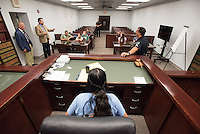 NWA Democrat-Gazette/J.T. WAMPLER Judge Stephen Thomas, from the left, and David Bailey, prosecutor, explain Monday Aug. 3, 2015 the basics of the judicial system during the Siloam Springs Police Department's  Police Camp. The camp was held for teens interested careers in the law enforcement and legal system. Ashley Ramirez, 14, sits in the judge's chair while other students took places in court to simulate a trial setting.