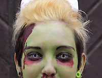 close up headshot of female participant in prague zombie walk event. Female painted green in the face with contacts.