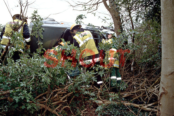 Firefighters and Ambulance Paramedic crews attending a road traffic accident where a car left the road and crashed down an embankment into a tree. This image may only be used to portray the subject in a positive manner..©shoutpictures.com..john@shoutpictures.com