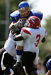 MADISON, SD - AUGUST 30: Joe Whealy of Dakota State University is sandwiched between Daniel Lopez and Billy Reddick of Bacone College in the first quarter of their game Saturday afternoon at Trojan Field in Madison. (photo by Dave Eggen/Inertia)