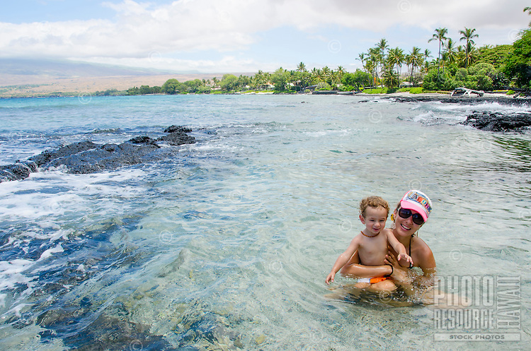 A local boy and his mother smile at friends just beyond view from a tidal pool at a beach in Puako, Hawai'i Island.