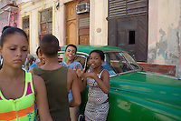 kids talking and joking next to a green oldtimer