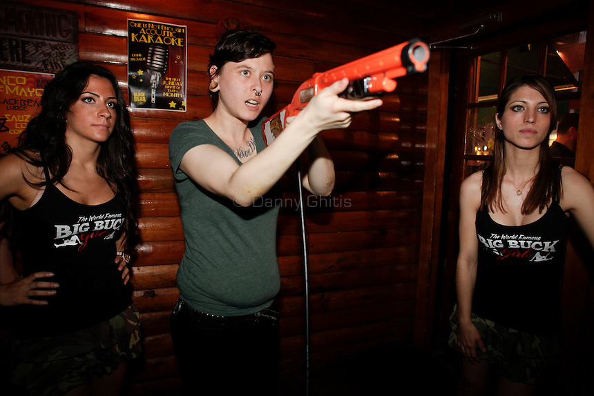 Big Buck Girls Andrea Miele, 23, left, and Alicia Patterson, 24, right, encourage Emily Star, 24, as she competes at The Black Bear Lodge in Manhattan, which hosted an official Big Buck Party on Thursday April, 28, 2011. Fans of the popular hunting arcade game were invited to test their skill against other Big Buck Hunter fans to compete for prizes, enter to win raffle merchandise and meet Big Buck Girls...Danny Ghitis for The New York Times