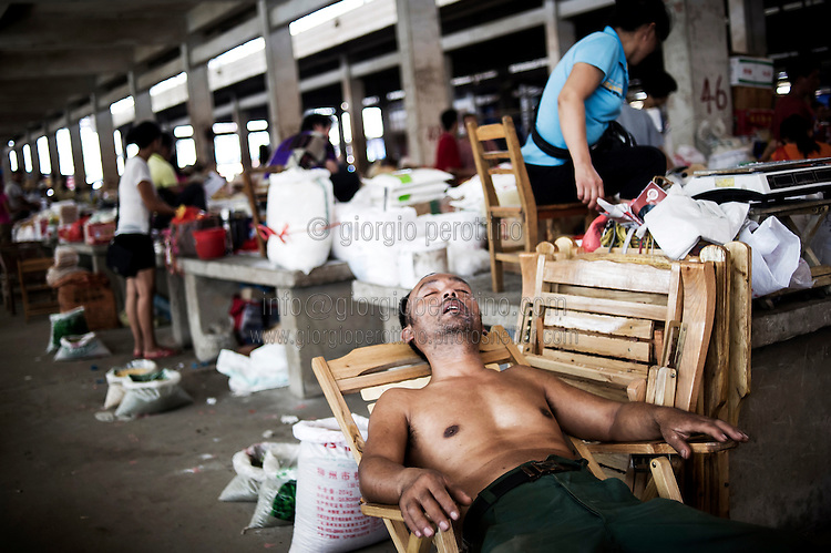 """A Chinese vendor takes a rest in a village market near YangShuo, Guilin, China, August 02, 2014. <br /> <br /> This image is part of the series """"24/7"""", an ironic view on restless and fast-growing Chinese economy described through street vendors and workers sleeping during their commercial daily activity. <br /> <br /> © Giorgio Perottino"""