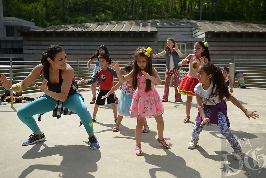 NWA Democrat-Gazette/BEN GOFF @NWABENGOFF<br /> Monica Gutierrez (front center) of En Fuego Fit leads a Zumba dance on Sunday April 24, 2016 during the 'El Dia de los Ninos' event at Crystal Bridges Museum of American Art in Bentonville. El Dia de los Ninos, or Children's Day, is a hispanic tradition, but the event included dance, musical and crafts highlighting a variety of cultures and children's creativity.