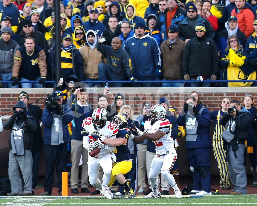 Ohio State Buckeyes defensive back Tyvis Powell (23) intercepts the two point conversion intended for Michigan Wolverines wide receiver Drew Dileo (9) as Ohio State Buckeyes cornerback Doran Grant (12) helps on the play during the fourth quarter of the NCAA football game at Michigan Stadium in Ann Arbor, Michigan on Saturday, November 30, 2013. (Columbus Dispatch photo by Jonathan Quilter)
