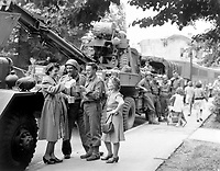 """Army Ordnance men await the """"go"""" signal for cross channel trip to France.  British civilians serve hot coffee as the men await the word to move out in an English town.  July 24, 1944. Messerlin. (Army)<br /> Exact Date Shot Unknown<br /> NARA FILE #:  111-SC-191728<br /> WAR & CONFLICT BOOK #:  1255"""