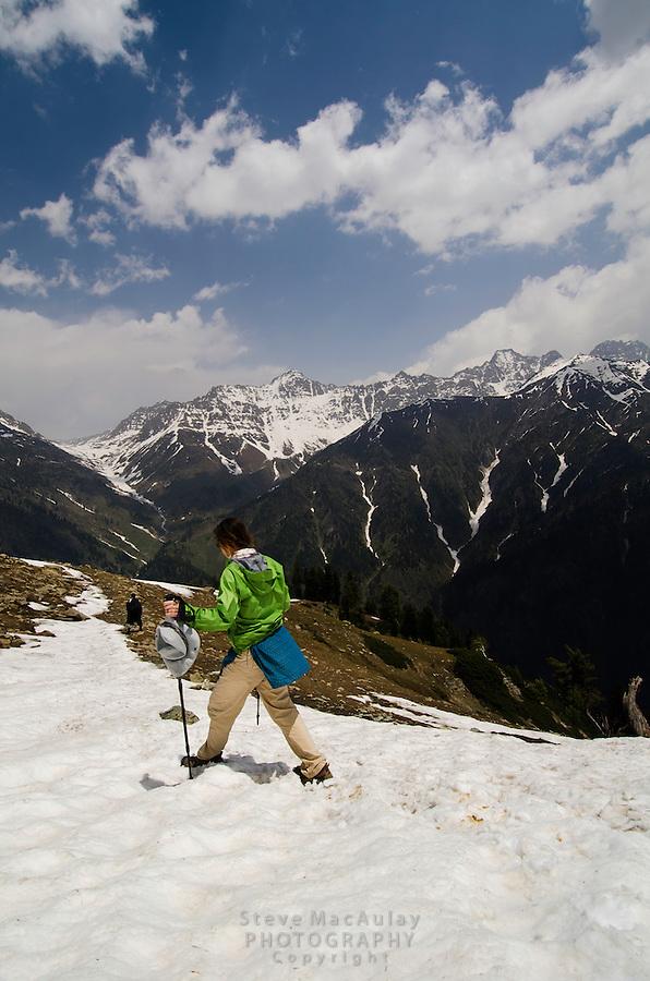 Female trekker walking on snow slope, Western Himalayan Mountains, Kashmir, India..