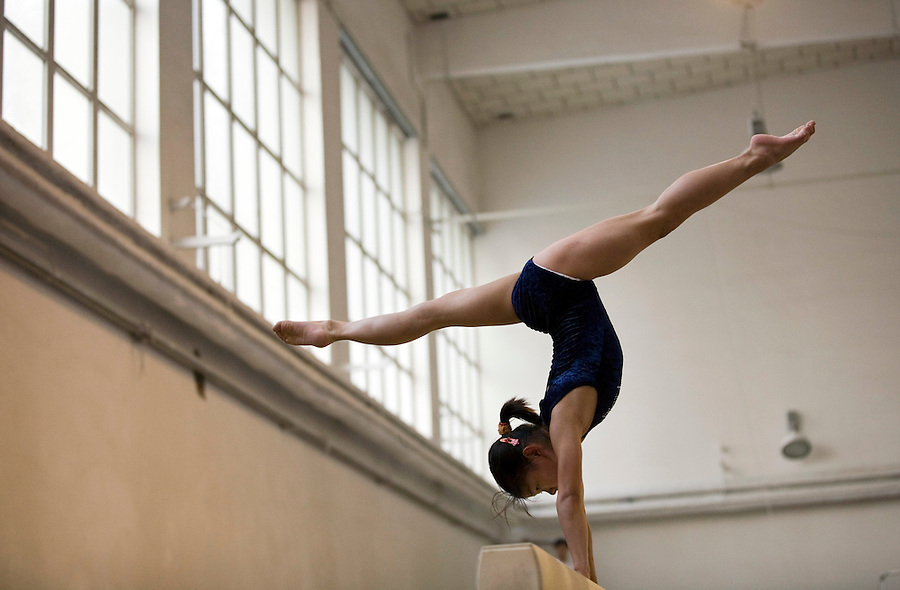 A young girl works on her balance beam skills.