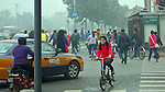 Bicycles and cars in a Beijing intersection during morning rush hour on a smoggy day