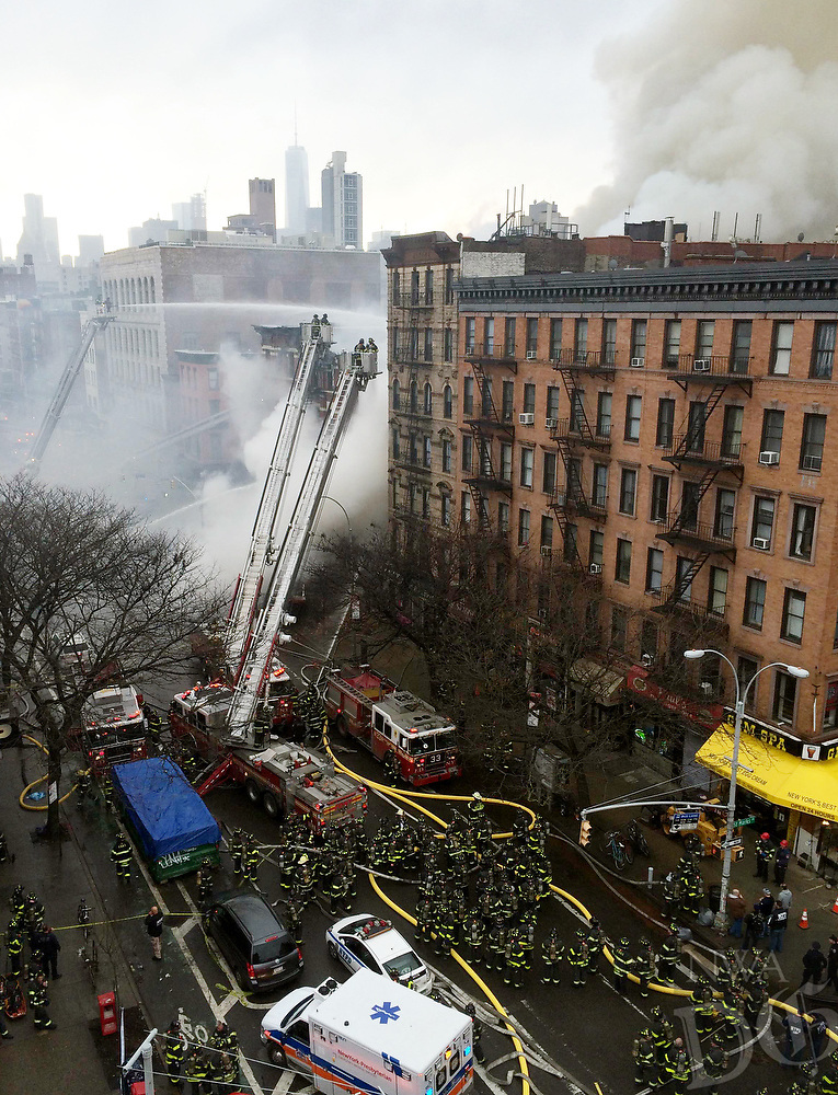 New York City firefighters work the scene of a large fire and a partial building collapse in the East Village neighborhood of New York on Thursday, March 26, 2015. Orange flames and black smoke are billowing from the facade and roof of the building near several New York University buildings. (AP Photo/John Minchillo)