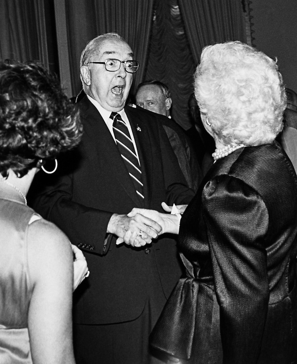 Retirement Party for Sen. James A. McClure, R-Idaho, by Sen. Steve Symms, R-Idaho. Here Sen. Jesse Helms, R-N.C., greets Barbara just before sitting down next to Sen. McClure. March 20, 1990. (Photo by Maureen Keating/CQ Roll Call)