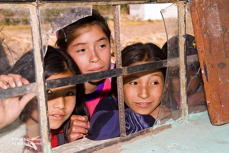 Four female students look in broken framed window of classroom in small town of Peru