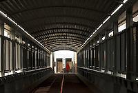 Woman walking through deserted city overpass towards lift/elevator..