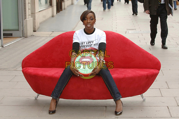 "ESTELLE.Launches MTV and The Body Shop campaign to help prevent aids with the caption ""Get Lippy Prevent HIV"" By buying their lip balm, funds are raised to fight the disease..London, England, March 31st 2008..photocall full length white t-shirt t shirt slogan charity red lips mouth motif speech bubble sitting sofa chair lip-shaped giant lip balm black shoes blue navy denim jeans .CAP/DS.©Dudley Smith/Capital Pictures"