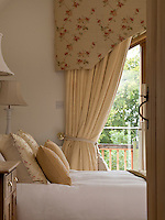 In the master bedroom a pair of cream curtains is embellished with a wide pelmet embroidered with a pretty floral design