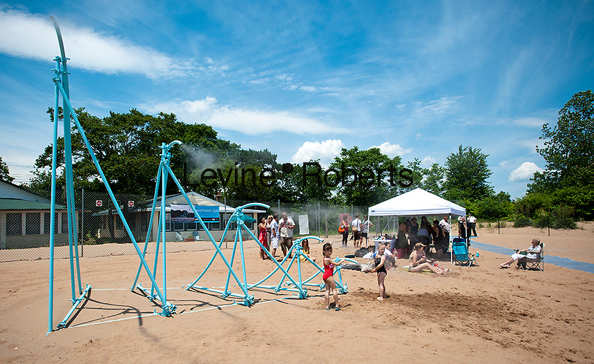 """Interactive public art exhibit """"MistWave"""" is seen at its installation on Cedar Grove Beach in Staten Island in New York on Sunday, June 3, 2012. Created by artists Andrea Padilla and Stanley Harris, the sculpture resembling a wave,  will spray a cooling mist over beachgoers on weekends during the summer season. The artwork is made of recycled scaffolding material. (© Richard B. Levine)"""