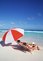 Couple in beach chairs with red umbrella