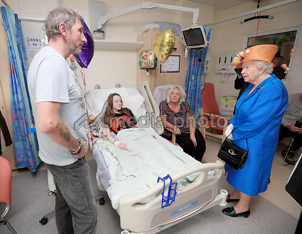25 May 2017 - Queen Elizabeth II speaks to Millie Robson, 15, from Co Durham, her mother, Marie, and dad, David, during a visit to the Royal Manchester Children's Hospital to meet victims of the terror attack in the city earlier this week and to thank members of staff who treated them. Photo Credit: ALPR/AdMedia