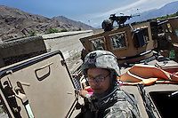 US ARMY Specialist Kahaya Komar scans her sector from an emergency hatch of her armored personnel carrier while her vehicle is stopped by traffic during  a day long logistical mission between Jalalabad and The Pech Valley in Kunar province, Afghanistan on Wednesday  May 1, 2010...Specialist Komar is a radio operator and assistant gunner on logistical convoys with Destro Platoon, Fury Company, 2nd Battalion, 4th Brigade, Task Force Mountain Warrior, 4th Infantry Division..
