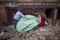 Nepalese people cover their belongings with plastic wraps to protect them from rain, Shanku, near Kathmandu, Nepal. May 9, 2015