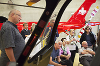 "Switzerland. Canton Ticino. Locarno Airport LSZL. The Rega base's official name is Locarno LSMO AFB (Rega 6). A group of swiss german tourists visit the Rega base and listen to a lecture on how the Rega functions in Ticino and about the Rega Agusta AW109 SP Grand ""Da Vinci » helicopter. All Rega helicopters carry a crew of three: a pilot, an emergency physician, and a paramedic who is also trained to assist the pilot for radio communication, navigation, terrain/object avoidance, and winch operations. The name Rega was created by combining letters from the name ""Swiss Air Rescue Guard"" as it was written in German (Schweizerische Rettungsflugwacht), French (Garde Aérienne Suisse de Sauvetage), and Italian (Guardia Aerea Svizzera di Soccorso). Rega is a private, non-profit air rescue service that provides emergency medical assistance in Switzerland. Rega is unique within Europe with the majority of its costs paid through the annual fees of private contributors. In exchange, Rega does not charge its contributors for its search, rescue and repatriation costs. Some of the visiting tourists are already Rega private contributors.Rega mainly assists with mountain rescues, though it will also operate in other terrains when needed, most notably during life-threatening emergencies. As a non-profit foundation, Rega does not receive financial assistance from any government. The AgustaWestland AW109 is a lightweight, twin-engine, helicopter built by the Italian manufacturer Leonardo S.p.A. (formerly AgustaWestland, Leonardo-Finmeccanica and Finmeccanica). Leonardo S.p.A is an Italian global high-tech company and one of the key players in aerospace. In close collaboration with the manufacturer, the Da Vinci has been specially designed to cater for Rega's particular requirements as regards carrying out operations in the mountains. It optimally fulfills the high demands made of it in terms of flying characteristics, emergency medical equipment and maintenance. Safety, performance"