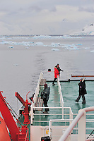 Photographers Exercising - A group of photographers looking for their next great shot from the deck of the MV Ushuaia in the Herrarra Channel, Antarctic Peninsular.