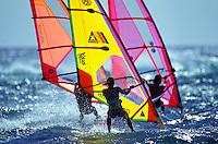 Close up of three windsurfers at Backyards Sunset Beach, Oahu