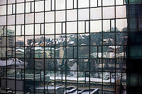 The Sarajevo cityscape reflected in the glass of a high rise block in the city centre. <br /> <br /> In 1992 while volunteering at the Varazdin refugee camp Panos photographer Bjoern Steinz met and became close to Elvis, a Bosnian Muslim refugee, and his family. They shared the hardships of camp life together which Steinz documented. While the prints were archived for many years two of the images always returned to Bjoern's thoughts. 25 years later he set out to try and find out what had happened to Elvis and his family in the intervening years. Modern social media made the task surprisingly easy and they were reunited in Hadzici where Elvis now lives with his family.