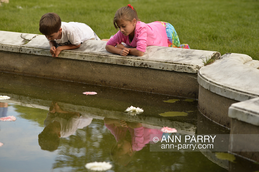 Old Westbury, New York, U.S. - June 21, 2014 - A young girl and boy looks at their reflections in the Reflecting Pool shortly before Lori Belilove & The Isadora Duncan Dance Company dances in Greek tunics throughout the gardens during the Midsummer Night event at the historic Long Island Gold Coast estate of Old Westbury Gardens on the first day of summer, the summer solstice.