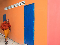 A Buddhist Monk walking past a colourful wall at a Monastery in Battambang, Cambodia.