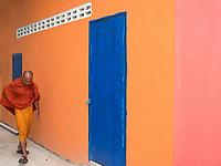 A Buddhist Monk walking past a colourful wall at a Monastery in Battambang, Cambodia.