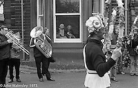 """The """"Nutters' Dance"""", Bacup, Lancashire  1973.  On Easter Saturday every year the """"Coco-nut"""" dancers gather at one boundary of the town and dance their way across to the other accompanied by members of the Stackstead Silver Band, collecting for charity as they go.  Here they're dancing outside an old peoples' home."""