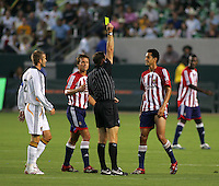 Referee Terry Vaughn yellow cards Chivas defender Olando Perez (77) as LA Galaxy midfielder David Beckham (23) and Chivas midfielder Jessie Marsch (15) look on. CD Chivas USA defeated the LA Galaxy 3-0 in the Super Classico MLS match at the Home Depot Center in Carson, California, Thursday, August 23, 2007.