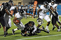 30 March 2012:  FIU's Jeff Fulwood (18) loses his helmet attempting to prevent Jeremiah Harden (6) from scoring a touchdown at the FIU Football Spring Game at University Park Stadium in Miami, Florida.