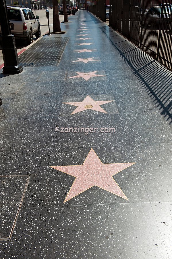 Hollywood Walk of Fame, Celebrity Stars, Hollywood, CA, coral-pink terrazzo five-point star rimmed with brass, inlaid into a charcoal-colored terrazzo background. In the upper portion of the pink star field,  round inlaid brass emblem indicates the category