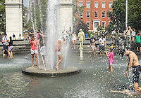 New Yorkers and visitors enjoy the fountain in Washington Square Park in Greenwich Village in New York on Saturday, August 13, 2016. Blistering heat and sticky humidity have moved in over the weekend making the temperature feel way over 100 degrees F. The city has issued a heat advisory with cooling centers opened throughout the five boroughs. ( © Richard B. Levine)