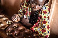 Benin. Cotonou . foyer salesiano Don Bosco bambino gioca a mancala