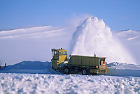 High winds blow drifting snow across the James Dalton Highway north of the Brooks Range, on Alaska's Arctic coastal plains. Alaska department of transportation worker removes snow drifts with blower.