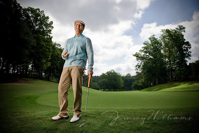 An asian man stands on a golf course holding his golf club after making a putt.