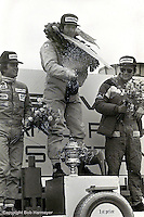 Jody Scheckter, winner of the 1976 Grand Prix of Sweden in his Tyrrell P34 six-wheel Formula 1 car, sprays champagne during the victory celebration. Teammate Patrick Depailler (left) placed second and Niki Lauda (right) placed third in a Ferrari.