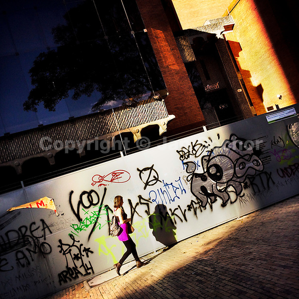 A Colombian woman passes in front of steel hoarding panels, covered in random scrawls and territory tags, in La Candelaria, Bogotá, Colombia, 19 February, 2016. A social environment full of violence and inequality (making the street art an authentic form of expression), with a surprisingly liberal approach to the street art from Bogotá authorities, have given a rise to one of the most exciting and unique urban art scenes in the world. While it's technically not illegal to scrawl on Bogotá's walls, artists may take their time and paint in broad daylight, covering the walls of Bogotá not only in territory tags and primitive scrawls but in large, elaborate artworks with strong artistic style and concept. Bogotá has become an open-air gallery of contemporary street art.