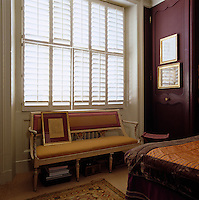 An antique banquette is situated under the large window of the bedroom which is screened with a series of wooden shutters