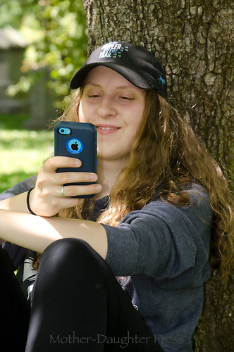 Girl smiling while looking at iphone under tree