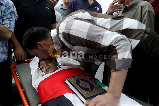 A relative mourns over the body of Mohammed Khalil al-Anati, a 11-year-old Palestinian who was reportedly shot dead by Israeli soldiers in al-Fawwar refugee camp on August 10, 2014 at al-Ahli hospital in the city of Hebron in the southern West Bank. Witnesses said he was shot by Israeli soldiers during an army operation. The Israeli military said it was looking into the reports. Photo by Mamoun Wazwaz