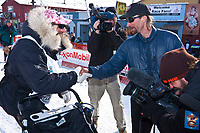 2010 winner Lance Mackey (R) congratulates second-place finisher Hans Gatt at the Nome finish line during the 2010 Iditarod