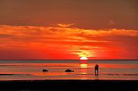 Couple watches sunset together, Skaket beach, Cape Cod, MA, Massachusetts, USA