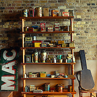 A collection of classic old tins displayed on shelves against a brick wall