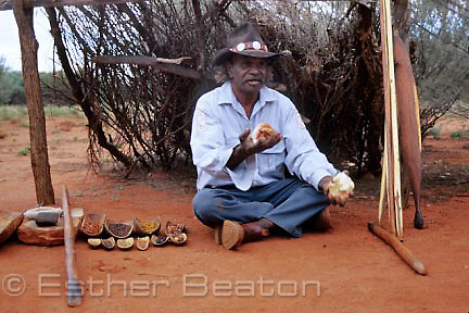 Aboriginal man with display of aboriginal tools and weapons in front of a traditional gunyah. Uluru-Kata Tjuta National Park, Northern Territory.  Anangu Tours, Uluru Nat Pk, Northern Territory